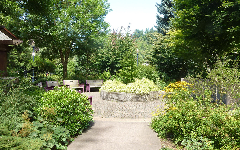 A circular path is lined by a series of benches with a round planting bed in the center of the circular path.