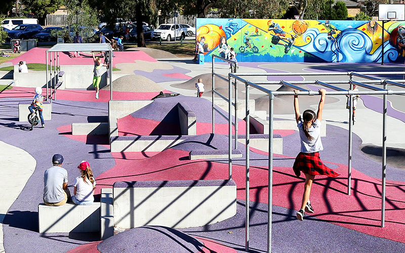 Children play in different ways on the various hills located around the edge of the ball court.