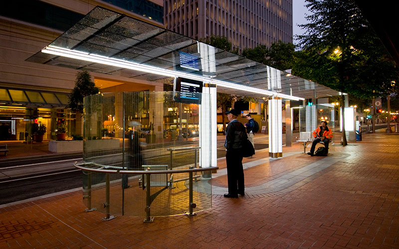 View of a tram stop along the light rail line in Downtown Portland at night. The bust stop is well lit with seats to rest while waiting for the tram.